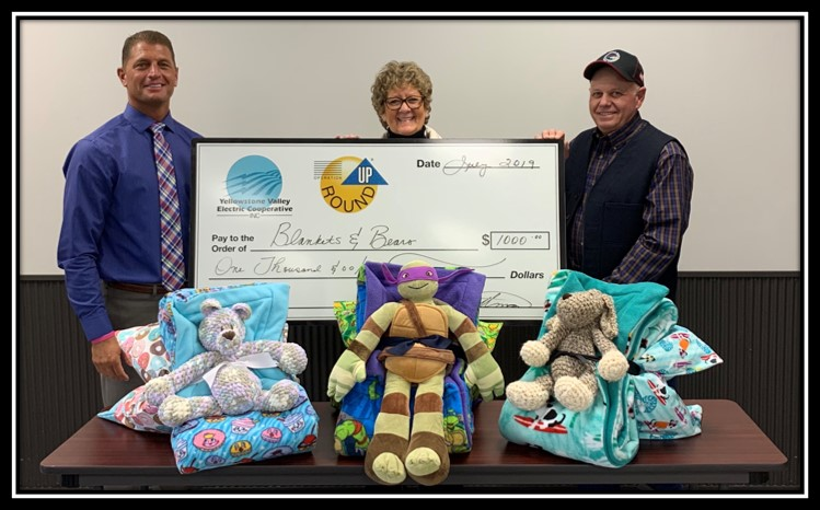 A woman and two men presenting a large check near stuffed animals and blankets