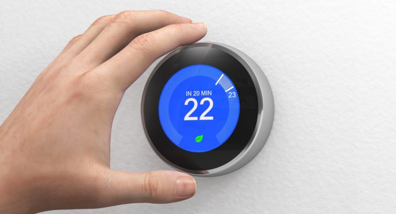 Hand reaching out to adjust a Nest Smart Thermostat