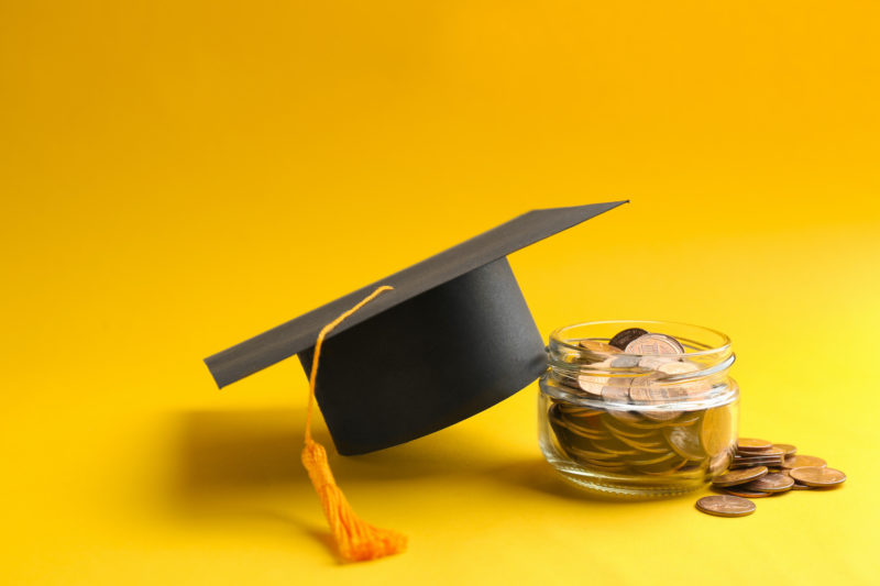 Glass jar, coins and graduation hat on color background.