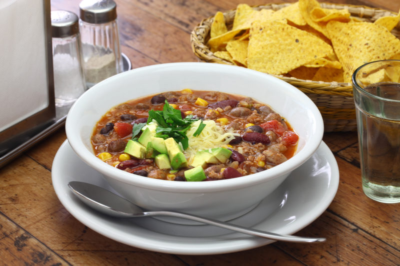 taco soup in a bowl with corn chips on the side