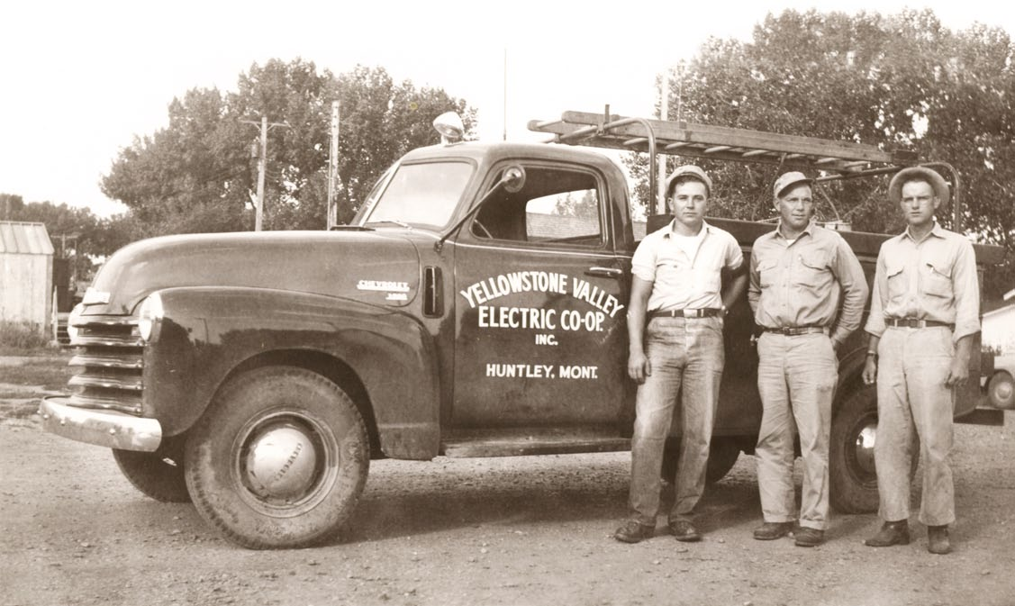black and white photo of linemen next to bucket truck