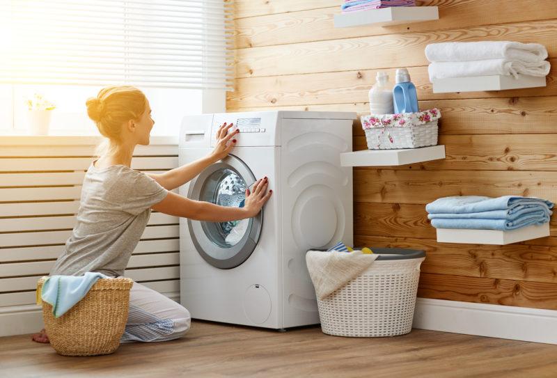 woman closing washing machine in laundry room