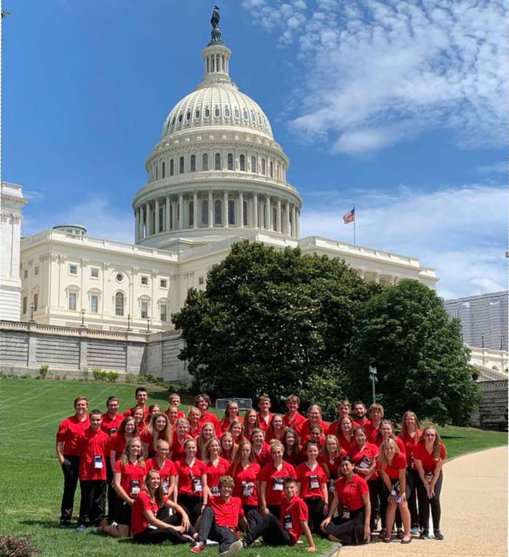 Large group of students wearing matching red tshirts in front of the Capitol building.