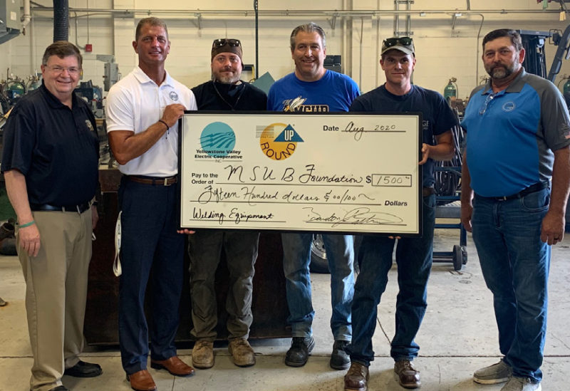 Group of men holding a check from Operation Round Up for the MSUB Foundation.