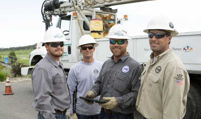 YVEC linemen in hard hats standing next to a boom truck