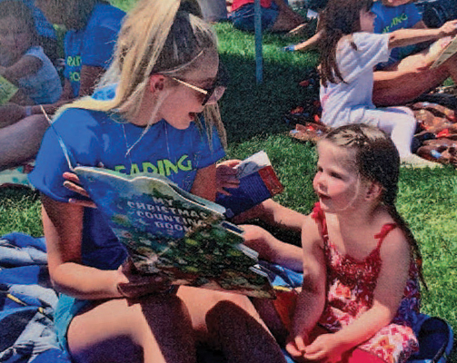 woman reading to young girl outside on grass