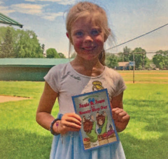 young girl holding a book outside