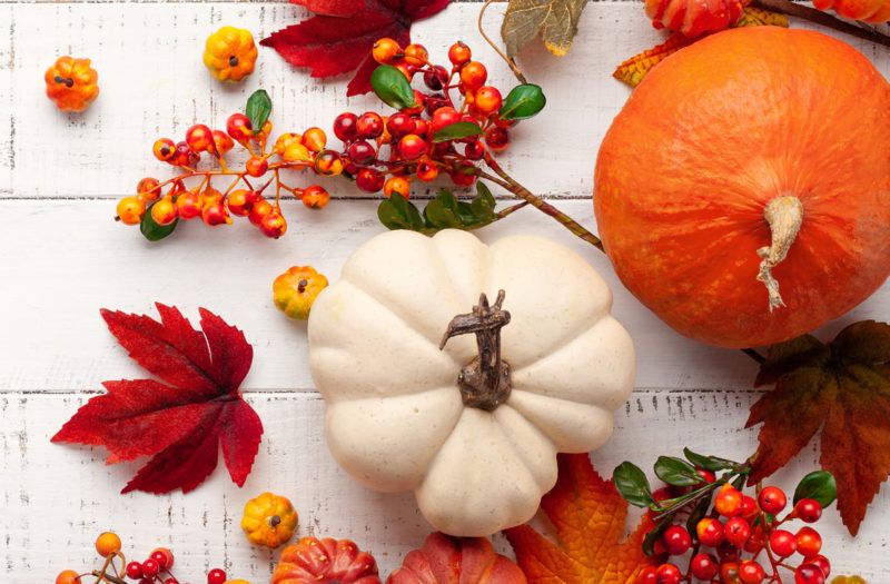 pumpkins and leaves on table