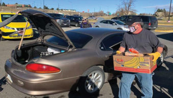 man with box of food placing it in trunk of car